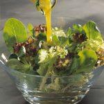 Pouring dressing over mixed leaf salad keywords: Vinaigrette, French Dressing